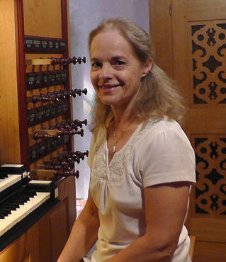 Photograph of Margaret Phillips seated at an organ.