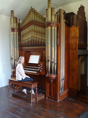 Photograph of Margaret seated at an organ.